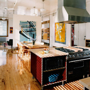 Inspiration for a small midcentury single-wall eat-in kitchen in New York with a single-bowl sink, flat-panel cabinets, red cabinets, wood benchtops, black appliances, light hardwood floors and with island.