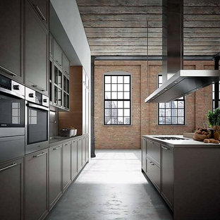 This is an example of a large industrial galley open plan kitchen in New York with shaker cabinets, medium wood cabinets, wood benchtops, concrete floors, multiple islands and grey floor.