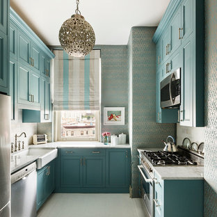 This is an example of a small traditional u-shaped enclosed kitchen in New York with a belfast sink, shaker cabinets, blue cabinets, marble worktops, stainless steel appliances and no island.