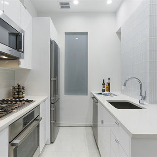 Photo of a small modern galley eat-in kitchen in New York with an undermount sink, flat-panel cabinets, white cabinets, glass tile splashback, stainless steel appliances, no island, quartz benchtops, white floor, white splashback, porcelain floors and white benchtop.