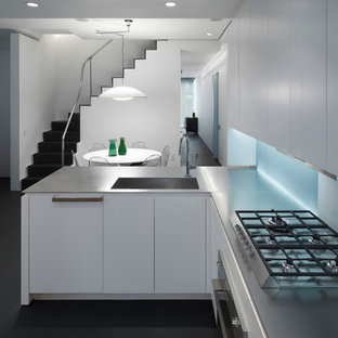 Mid-sized modern eat-in kitchen appliance - Mid-sized minimalist l-shaped dark wood floor and black floor eat-in kitchen photo in New York with an undermount sink, flat-panel cabinets, white cabinets, concrete countertops, gray backsplash, paneled appliances and a peninsula