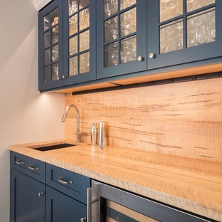 This is an example of a mid-sized transitional u-shaped separate kitchen in DC Metro with shaker cabinets, blue cabinets, wood benchtops, yellow splashback, timber splashback, stainless steel appliances, ceramic floors, a peninsula, grey floor and yellow benchtop.