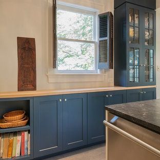 Inspiration for a medium sized classic u-shaped enclosed kitchen in DC Metro with a submerged sink, shaker cabinets, blue cabinets, wood worktops, white splashback, ceramic splashback, stainless steel appliances, ceramic flooring, a breakfast bar, grey floors and yellow worktops.