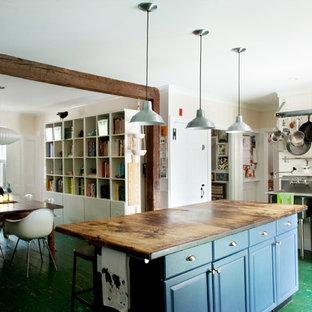 Cette image montre une cuisine américaine chalet avec un électroménager en acier inoxydable, un plan de travail en bois, un placard avec porte à panneau surélevé, des portes de placard bleues, un sol en bois peint et un sol vert.