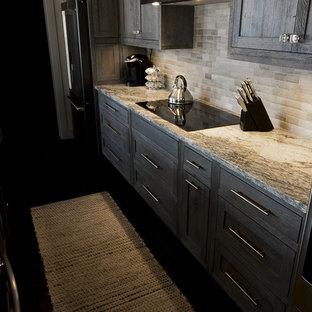 他の地域の中サイズのインダストリアルスタイルのおしゃれなキッチン (アンダーカウンターシンク、落し込みパネル扉のキャビネット、ヴィンテージ仕上げキャビネット、御影石カウンター、ベージュキッチンパネル、セラミックタイルのキッチンパネル、シルバーの調理設備の、濃色無垢フローリング、黒い床) の写真