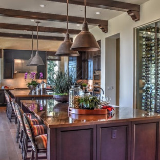 Design ideas for a large traditional u-shaped kitchen in Orange County with medium hardwood floors, recessed-panel cabinets, dark wood cabinets and multiple islands.