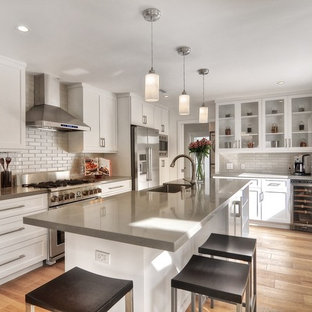Large contemporary kitchen ideas - Inspiration for a large contemporary l-shaped kitchen remodel in Orange County with a farmhouse sink, shaker cabinets, white cabinets, white backsplash, subway tile backsplash, stainless steel appliances and an island
