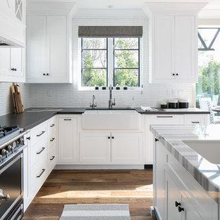 Exemple d'une cuisine chic en L avec un évier de ferme, un placard à porte shaker, des portes de placard blanches, une crédence blanche, un électroménager noir, un sol en bois brun et un îlot central.