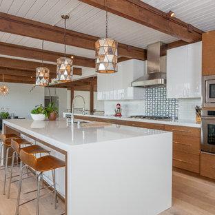 Идея дизайна: параллельная кухня-гостиная среднего размера в стиле ретро с плоскими фасадами, фасадами цвета дерева среднего тона, столешницей из кварцевого композита, белым фартуком, фартуком из стеклянной плитки, техникой из нержавеющей стали, островом, врезной раковиной и светлым паркетным полом