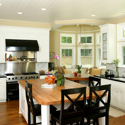 Example of a classic kitchen design in Orange County with wood countertops, shaker cabinets, white cabinets and black appliances