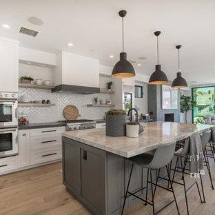Cette image montre une cuisine design en L avec un placard à porte shaker, des portes de placard blanches, une crédence grise, un électroménager en acier inoxydable, un sol en bois brun, un îlot central, un sol marron et un plan de travail gris.