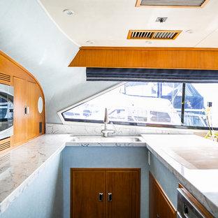 オレンジカウンティの小さいビーチスタイルのおしゃれなキッチン (アンダーカウンターシンク、フラットパネル扉のキャビネット、中間色木目調キャビネット、クオーツストーンカウンター、マルチカラーのキッチンパネル、シルバーの調理設備の、無垢フローリング、オレンジの床、マルチカラーのキッチンカウンター) の写真