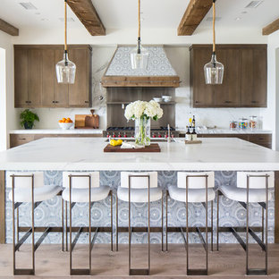 Inspiration for a large mediterranean l-shaped medium tone wood floor and brown floor open concept kitchen remodel in Orange County with flat-panel cabinets, medium tone wood cabinets, white backsplash, stainless steel appliances, an island and white countertops