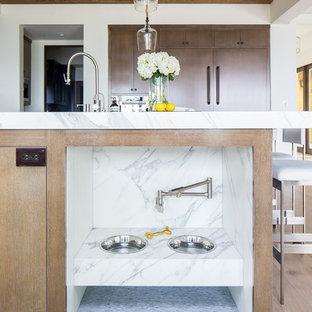オレンジカウンティの大きい地中海スタイルのおしゃれなキッチン (アンダーカウンターシンク、フラットパネル扉のキャビネット、中間色木目調キャビネット、白いキッチンパネル、シルバーの調理設備の、無垢フローリング、茶色い床、白いキッチンカウンター) の写真