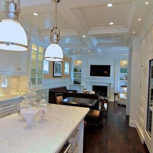 На фото: кухня-гостиная в классическом стиле с фасадами с утопленной филенкой, мраморной столешницей, белыми фасадами, белым фартуком и фартуком из каменной плиты с