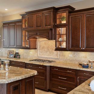 Große Klassische Küche in L-Form mit Vorratsschrank, Waschbecken, profilierten Schrankfronten, dunklen Holzschränken, Granit-Arbeitsplatte, Küchenrückwand in Beige, Rückwand aus Steinfliesen, Küchengeräten aus Edelstahl, Travertin und Kücheninsel in Orange County