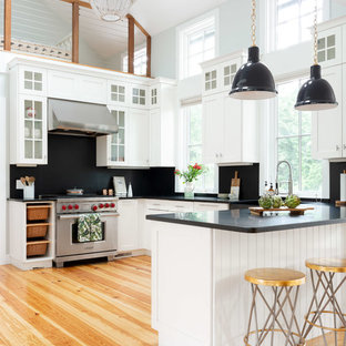 Inspiration for a beach style u-shaped kitchen in Providence with a farmhouse sink, shaker cabinets, white cabinets, black splashback, stone slab splashback, medium hardwood floors, a peninsula, brown floor and black benchtop.