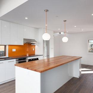 Offene, Zweizeilige Moderne Küche mit Unterbauwaschbecken, flächenbündigen Schrankfronten, weißen Schränken, Arbeitsplatte aus Holz, Küchenrückwand in Orange, Glasrückwand, Küchengeräten aus Edelstahl, braunem Holzboden und Kücheninsel in Vancouver