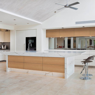 Design ideas for a large contemporary l-shaped open plan kitchen in Sydney with an undermount sink, flat-panel cabinets, white cabinets, quartz benchtops, grey splashback, mirror splashback, black appliances, limestone floors and with island.