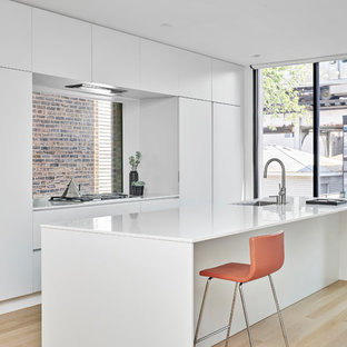 Modern inredning av ett vit vitt parallellkök, med släta luckor, vita skåp, ljust trägolv, en köksö, en undermonterad diskho, fönster som stänkskydd, integrerade vitvaror och beiget golv