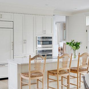 プロビデンスの大きいトランジショナルスタイルのおしゃれなキッチン (白いキャビネット、白いキッチンパネル、パネルと同色の調理設備、淡色無垢フローリング、アンダーカウンターシンク、落し込みパネル扉のキャビネット、大理石カウンター) の写真