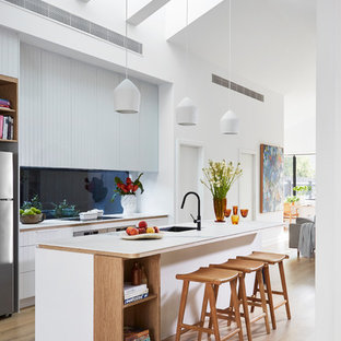 Contemporary open plan kitchen in Melbourne with a single-bowl sink, white cabinets, blue splashback, glass sheet splashback, stainless steel appliances, light hardwood floors, with island, beige floor and white benchtop.