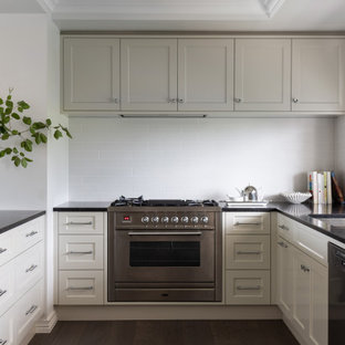 Mid-sized transitional u-shaped kitchen in Brisbane with a double-bowl sink, shaker cabinets, white cabinets, white splashback, subway tile splashback, stainless steel appliances, medium hardwood floors, no island, brown floor and black benchtop.