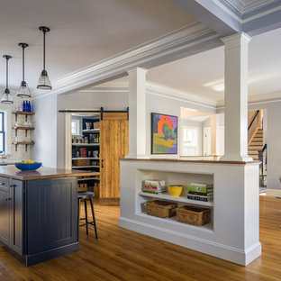 Victorian open plan kitchen in Boston with a farmhouse sink, shaker cabinets, white cabinets, quartz benchtops, white splashback, subway tile splashback, stainless steel appliances, medium hardwood floors and with island.