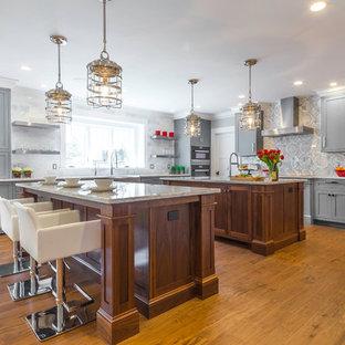 Geräumige Klassische Wohnküche in L-Form mit Küchenrückwand in Grau, zwei Kücheninseln, Landhausspüle, Schrankfronten im Shaker-Stil, grauen Schränken, Marmor-Arbeitsplatte, Rückwand aus Marmor, Elektrogeräten mit Frontblende, braunem Holzboden und braunem Boden in Boston