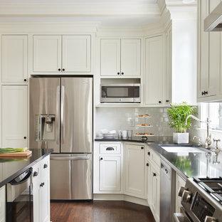 Große Klassische Küche in L-Form mit Unterbauwaschbecken, weißen Schränken, Quarzwerkstein-Arbeitsplatte, Küchenrückwand in Weiß, Rückwand aus Metrofliesen, Küchengeräten aus Edelstahl, dunklem Holzboden, Kücheninsel, braunem Boden, Schrankfronten im Shaker-Stil und schwarzer Arbeitsplatte in Boston