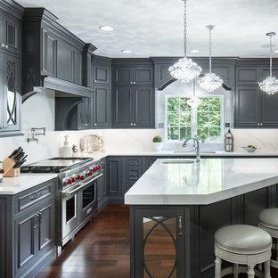 Inspiration för ett stort vintage vit vitt l-kök, med en undermonterad diskho, luckor med profilerade fronter, grå skåp, bänkskiva i kvarts, rostfria vitvaror, mörkt trägolv, en köksö och vitt stänkskydd
