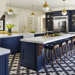 Transitional eat-in kitchen remodeling - Inspiration for a transitional galley ceramic floor and black floor eat-in kitchen remodel in New York with blue cabinets, stainless steel appliances, two islands, white countertops, an undermount sink, beaded inset cabinets, white backsplash and limestone backsplash