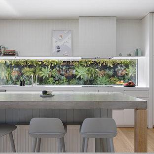 Réalisation d'une cuisine ouverte parallèle minimaliste avec un placard à porte plane, des portes de placard blanches, un plan de travail en béton, une crédence en fenêtre, un électroménager en acier inoxydable, un sol en bois clair, un îlot central et un sol beige.
