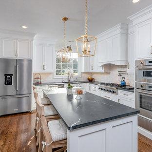 Exempel på ett klassiskt svart svart kök och matrum, med en undermonterad diskho, luckor med profilerade fronter, vita skåp, bänkskiva i kvartsit, vitt stänkskydd, stänkskydd i tunnelbanekakel, rostfria vitvaror, korkgolv och en köksö