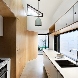 This is an example of a scandinavian kitchen in Sydney with a double-bowl sink, flat-panel cabinets, white cabinets, window splashback, concrete floors, no island, grey floor and white benchtop.