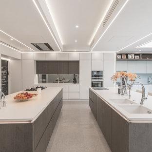 Свежая идея для дизайна: угловая кухня в современном стиле с обеденным столом, врезной раковиной, плоскими фасадами, белыми фасадами, фартуком цвета металлик, зеркальным фартуком, черной техникой, двумя и более островами, серым полом и белой столешницей - отличное фото интерьера