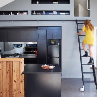 Foto de cocina contemporánea, abierta, con armarios con paneles lisos, puertas de armario negras, salpicadero metalizado, salpicadero con efecto espejo, electrodomésticos negros, suelo de cemento y una isla