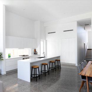 На фото: кухня-гостиная в морском стиле с двойной раковиной, плоскими фасадами, белыми фасадами, фартуком с окном, бетонным полом, островом, серым полом и белой столешницей