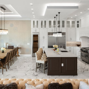Large contemporary open concept kitchen ideas - Inspiration for a large contemporary l-shaped porcelain floor and white floor open concept kitchen remodel in Orlando with a farmhouse sink, raised-panel cabinets, white cabinets, quartz countertops, multicolored backsplash, mosaic tile backsplash, stainless steel appliances, an island and white countertops