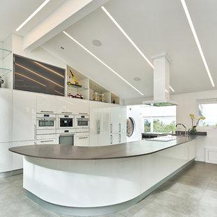 Modelo de cocina comedor de galera, contemporánea, grande, con armarios con paneles lisos, puertas de armario blancas, electrodomésticos blancos, península, fregadero encastrado, encimera de cemento y suelo de baldosas de cerámica