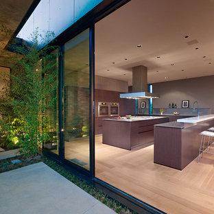 Immagine di una cucina design di medie dimensioni con ante lisce, ante marroni, top in quarzo composito, paraspruzzi grigio, elettrodomestici in acciaio inossidabile, parquet chiaro e 2 o più isole