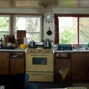 他の地域の小さいビーチスタイルのおしゃれなキッチン (シングルシンク、フラットパネル扉のキャビネット、中間色木目調キャビネット、ラミネートカウンター、カラー調理設備、リノリウムの床、アイランドなし) の写真