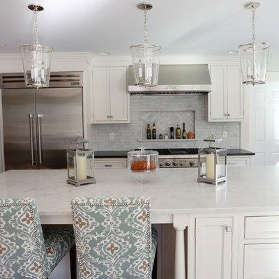 Example of a large classic u-shaped medium tone wood floor and brown floor eat-in kitchen design in New York with a farmhouse sink, recessed-panel cabinets, white cabinets, marble countertops, gray backsplash, ceramic backsplash, stainless steel appliances and an island