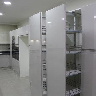 Bild på ett avskilt, mycket stort funkis svart svart u-kök, med en trippel diskho, släta luckor, grå skåp, granitbänkskiva, beige stänkskydd, stänkskydd i porslinskakel, rostfria vitvaror, klinkergolv i keramik, en köksö och beiget golv