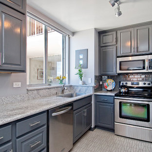 Photo of a small transitional l-shaped separate kitchen in San Francisco with an undermount sink, raised-panel cabinets, grey cabinets, granite benchtops, grey splashback, ceramic splashback, stainless steel appliances, vinyl floors, no island and beige floor.