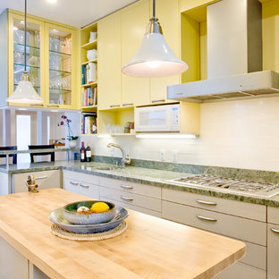 Design ideas for a mid-sized contemporary kitchen in San Francisco with an undermount sink, flat-panel cabinets, yellow cabinets, granite benchtops, white splashback, stainless steel appliances, light hardwood floors, with island and green benchtop.