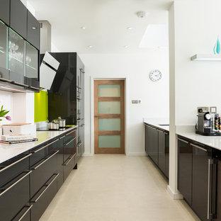 Idee per una grande cucina design con ante lisce, paraspruzzi verde, paraspruzzi con lastra di vetro, 2 o più isole, lavello integrato, ante grigie, top in quarzite, elettrodomestici da incasso e pavimento in gres porcellanato