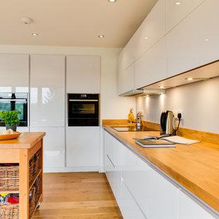 ハンプシャーの中くらいのモダンスタイルのおしゃれなキッチン (フラットパネル扉のキャビネット、白いキャビネット、木材カウンター、無垢フローリング) の写真