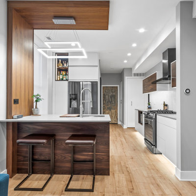 Example of a mid-sized trendy u-shaped open concept kitchen design in Chicago with an undermount sink, flat-panel cabinets, white cabinets, quartz countertops, white backsplash, cement tile backsplash, stainless steel appliances, a peninsula and gray countertops