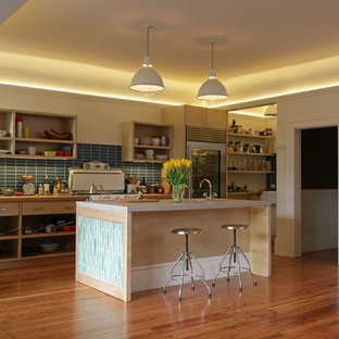 This is an example of a contemporary galley open plan kitchen in San Francisco with open cabinets, light wood cabinets, concrete benchtops, blue splashback, ceramic splashback and stainless steel appliances.